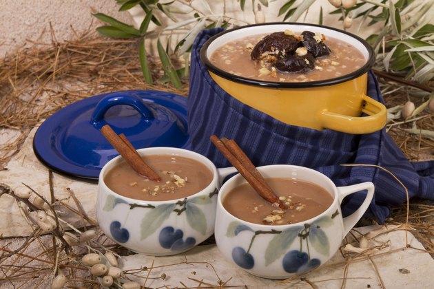 Kis fazékban és két bögrében aszaltszilvás leves, fahéjrudakkal, dióval meghintve erdõben.