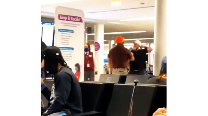 Trump-hívő (fekete pólóban, fehér sapkában) a Dulles repülőtéren, Washingtonban.